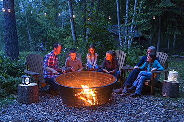 A family gathers outside around a campfire at dusk, Salmon Arm, British Columbia, Canada