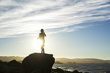 A woman stands on a rock looking out along the coast at sunset, silhouetted and backlit by the sunlight, San Mateo, California, United States of America