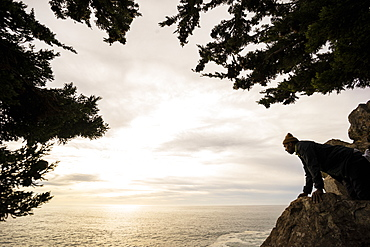 A man looks down over a rock to the ocean below at dusk, Julia Pfeiffer Burns State Park, California, United States of America