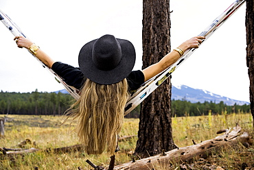 Rear view of a woman sitting in a hammock with a view of a mountain, Arizona, United States of America