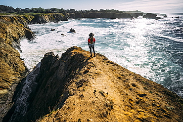 A woman stands looking out along the Russian Gulch Headlands, Mendocino county, California, United States of America