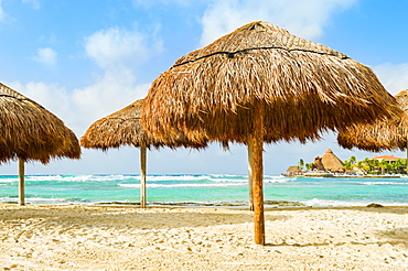 Grass beach umbrellas next to the Caribbean ocean, Playa Del Carmen, Quintana Roo, Mexico