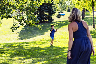 A mother throwing a disc toy to her son to catch in a park on warm fall afternoon during a family outing, Edmonton, Alberta, Canada