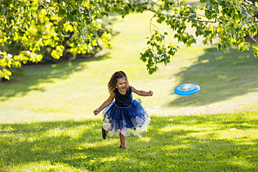 A young girl in a party dress chasing a disc toy that was thrown to her in a park on warm fall afternoon during a family outing, Edmonton, Alberta, Canada