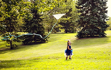 A young girl in a dress running and flying a kite in a city park on a warm fall afternoon, Edmonton, Alberta, Canada