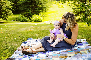 A mother and her baby daughter sitting on a picnic blanket and spending quality time together while enjoying a family outing in a city park on a warm fall afternoon, Edmonton, Alberta, Canada