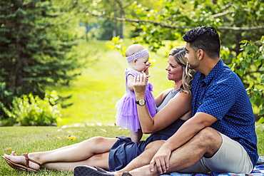 A mixed race husband and wife relax together with their baby girl on a blanket in a park on a warm autumn afternoon, Edmonton, Alberta, Canada