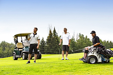 A group of golfers, one of which is handicapped with a mobility assistance device, watching as a long drive as it makes its way down a fairway, Edmonton, Alberta, Canada