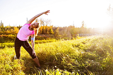 An attractive middle-aged woman wearing active wear and listening to music while pausing to do some stretch exercises during a run in a city park at sunset on a warm autumn evening, Edmonton, Alberta, Canada