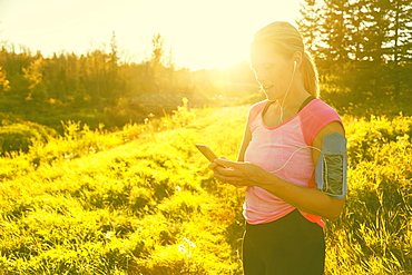 An attractive middle-aged woman wearing active wear pauses to text message while out running beside a creek in a city park on a warm fall evening and listening to music on her smart phone, Edmonton, Alberta, Canada