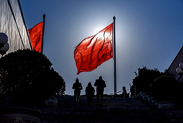 Silhouettes of people and flag in Tiananmen Square, Beijing, China