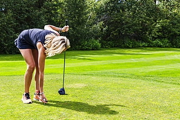 A female golfer places a golf ball on a tee while holding her driver, Edmonton, Alberta, Canada