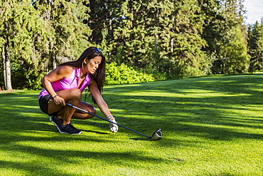 A female golfer places a golf ball on a tee and gets ready with her driver to tee off, Edmonton, Alberta, Canada