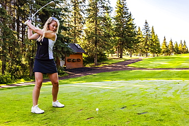 A female golfer at the top of her swing as she gets ready to hit the ball after setting up her shot, Edmonton, Alberta, Canada