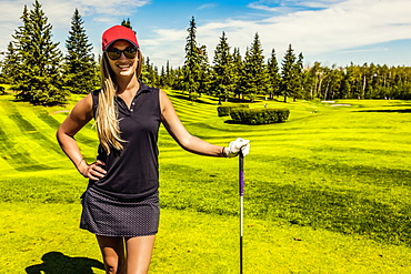 Portrait of a female golfer standing with her driver on the green grass of a golf club, Edmonton, Alberta, Canada