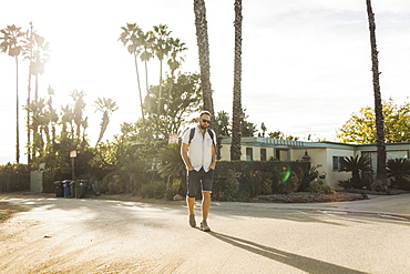 Man walks with a backpack on a residential street in a tropical climate, Long Beach, California, United States of America