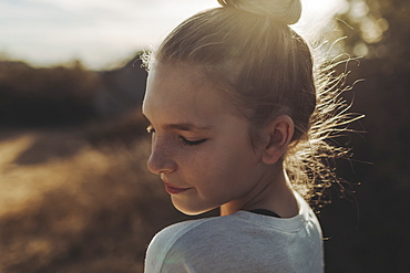 Close-up portrait of a preteen girl backlit by the sunlight, Los Angeles, California, United States of America