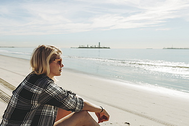 A woman sits on a beach looking out to the water, Long Beach, California, United States of America
