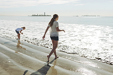 Two sisters walking out to the surf on a beach, Long Beach, California, United States of America