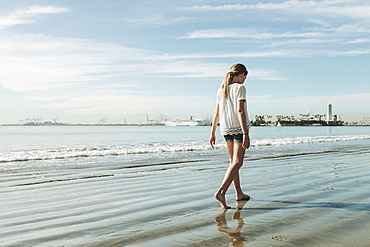 A girl walking on the beach on the wet sand, Long Beach, California, United States of America