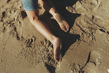 A child's wet feet covered in sand, Long Beach, California, United States of America