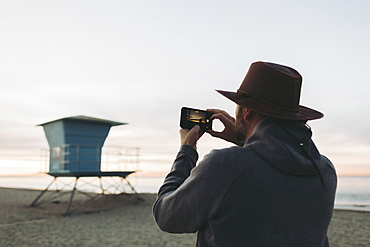 A man stands photographing a lifeguard station at dusk, Long Beach, California, United States of America