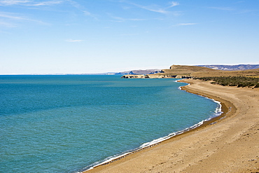 A desert coastline and beach contrast with the blue ocean and sky, Santa Cruz, Argentina
