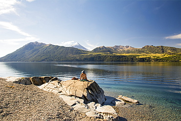 A woman basking in the sun on the shore of a lake with a snow-capped volcano in the distance, Neuquen, Argentina