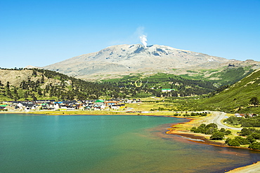A small town on a lake shore with smoking volcano in the background, Cavahue, Neuquen, Argentina