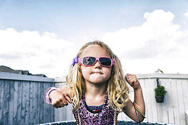 A young girl all dressed up with blond curly hair, sunglasses and jewelry standing on a trampoline in the backyard and showing off, Spruce Grove, Alberta, Canada