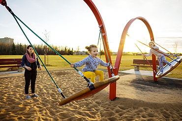 A young mom and her daughters playing on saucer swings in a playground on a warm autumn evening, Edmonton, Alberta, Canada