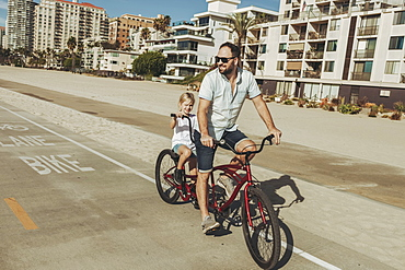 A father and daughter riding a tandem bike at Long Beach, Long Beach, California, United States of America