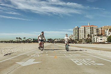 A father and daughter riding bikes at Long Beach, Long Beach, California, United States of America