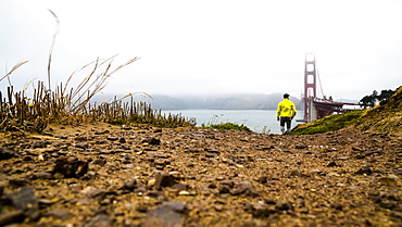 A man walking near the Golden Gate Bridge on a foggy day, San Francisco, California, United States of America
