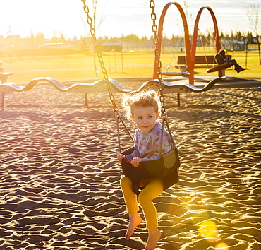 A young girl swinging by herself in a playground and enjoying a warm fall evening, Edmonton, Alberta, Canada