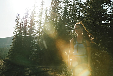 A woman illuminated by a sunbeam while running on a trail in the Rock Mountains, near Hinton, Alberta, Canada