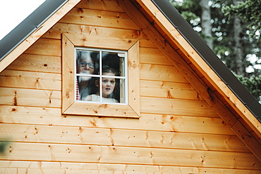 Mother and daughter looking out a playhouse window, Alberta, Canada