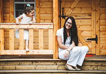 Portrait of a mother and daughter with a wooden playhouse, Alberta, Canada