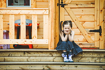 Portrait of a young girl sitting on a step in front of a wooden door, Alberta, Canada