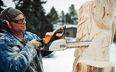 Artist carving a wood sculpture with chainsaw, Edmonton, Alberta, Canada