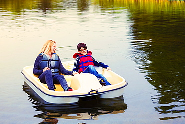 A mother and son taking a ride in a paddle boat on a lake, holding hands and talking together, Edmonton, Alberta, Canada