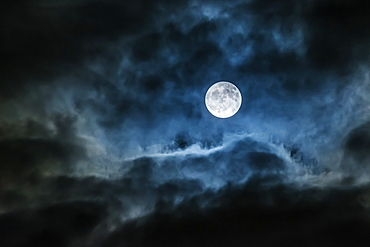 Bright full moon glowing in a cloudy sky, Ontario, Canada