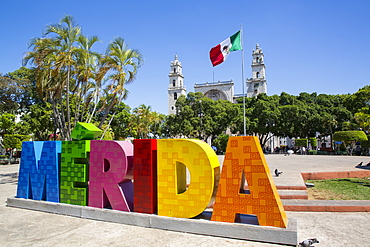 Colourful Merida sign with Mexican flag and Cathedral Of San Ildefonso in the background, Merida, Yucatan, Mexico