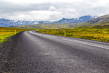 The open highway leads into the mountain landscape in Western Iceland, Iceland
