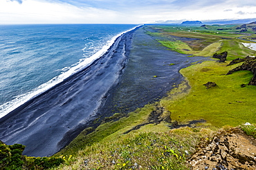 The view from the top of the tourist lookout at Dyrholaey near Vik, Southern Iceland. The black sand beach extends for miles into the distance and green pasture and farmland is seen in the background, Vik, Iceland