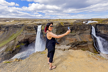 A young asian female hiker poses for a self-portrait on the edge of the Haifoss waterfall valley, a popular hiking destination in Iceland, Iceland