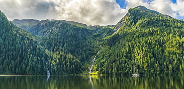 Scenic view of the Great Bear Rainforest area with a sailboat on the water, Hartley Bay, British Columbia, Canada