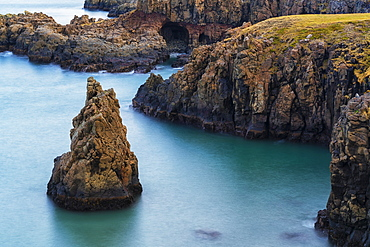 Amazing scenery along a remote section of the West Fjords with great autumn colours and a sea stack in the ocean, West Fjords, Iceland