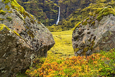 A large unnamed waterfall framed by large stone along the south coast of Iceland, Iceland