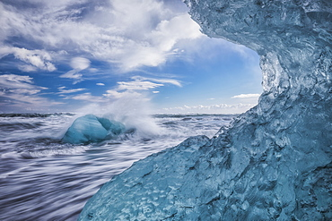 Blue ice and icebergs with water splashing at Jokulsarlon, South coast, Iceland